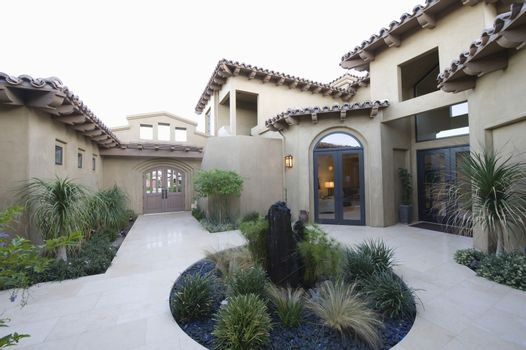 View of cactus garden and courtyard of a home against clear sky