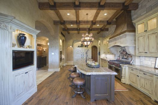 View of stools at island with chandelier and wood beamed ceiling in kitchen