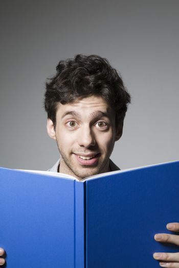 Young man smiling over book cover