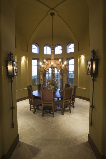 View of a lit chandelier hanging over table in dining room at home