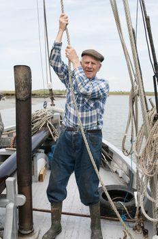Elderly fisherman pulling rope on deck