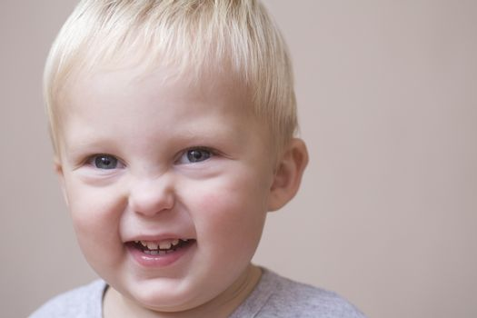 Blonde toddler scrunches his face in laughter