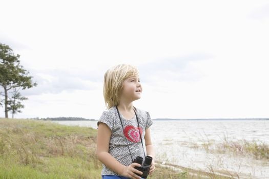Girl stands with binoculars at lakeside