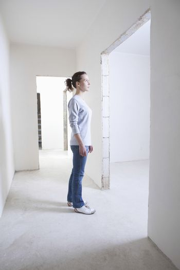Woman stands in hallway of new apartment