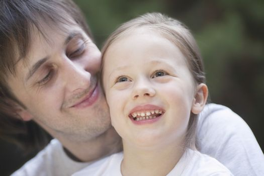 Man smiles proudly holding girl on his knee