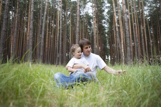 Man and girl sit in woodland clearing