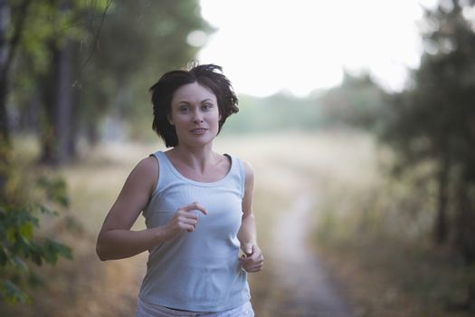 Mid adult woman jogs in woodland