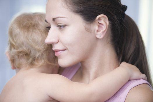 Mother holds blonde toddler