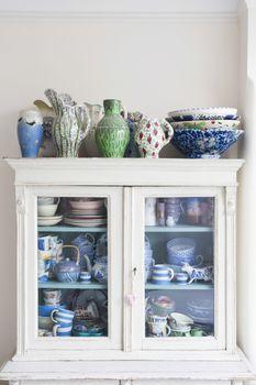 Crockery displayed in storage cabinet at home