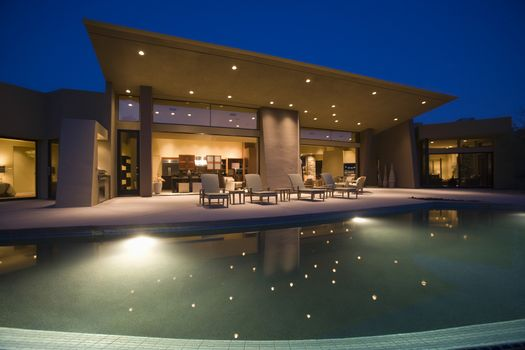 Lit swimming pool and house exterior at night