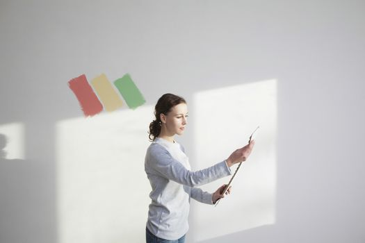 Woman deciding on paint sample in new apartment