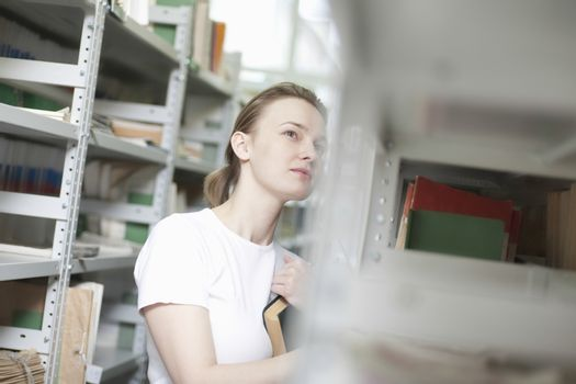 Young woman stands at library shelving