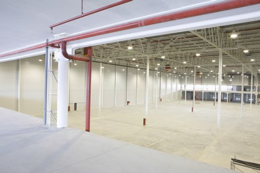 Large empty warehouse with red piping