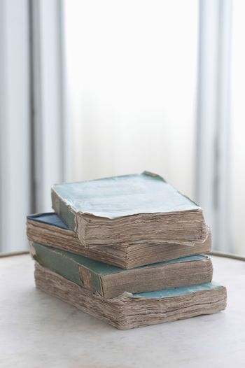 Stack of four old books on table
