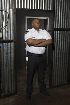 Security guard stands at corrugated metal doorway