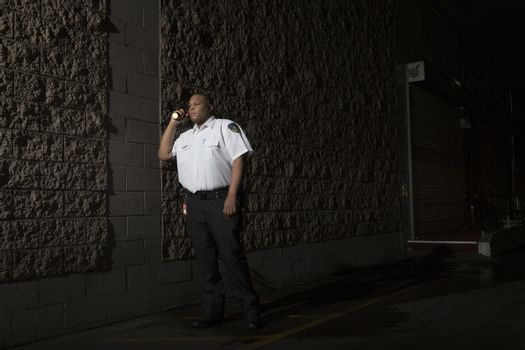 Security guard patrols at night with torch