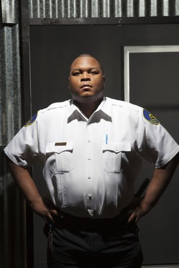 Security guard stands with hands on hips
