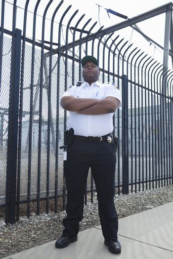 Security guard stands at strengthened prison fence