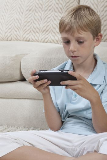 Boys sits cross-legged with portable games console