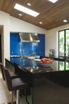 Blue splashback in black gloss kitchen