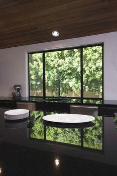 Empty plates on black gloss kitchen worktop