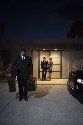 Chauffeur carries bags for couple standing at lit entrance