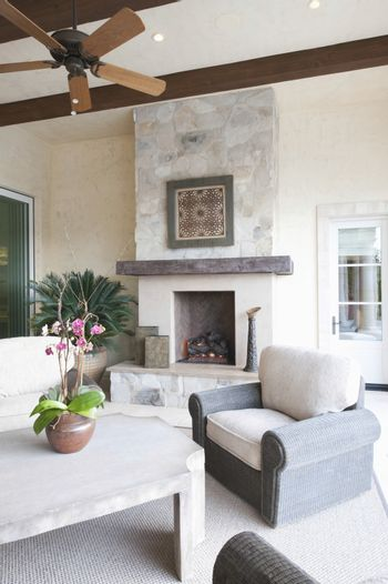 Outdoor room with fireplace and ceiling fan