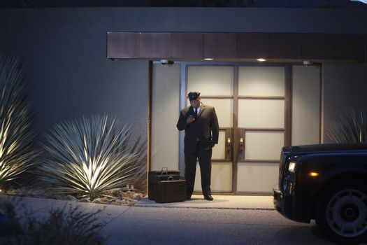 Chauffeur stands at lit entrance doorway with luggage