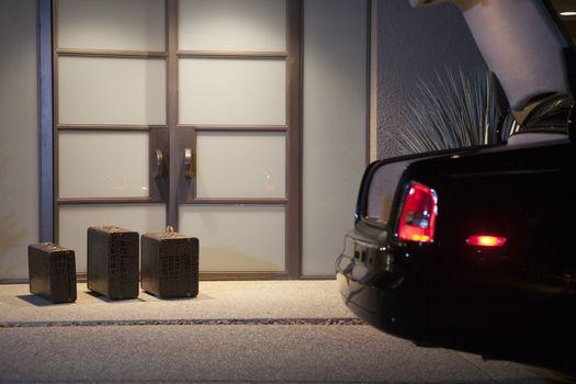 Three suitcases at lit doorway entrance