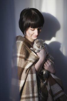 Woman in blanket stands holding kitten