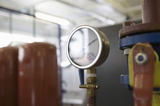 Closeup of pressure gauge inside an industrial room