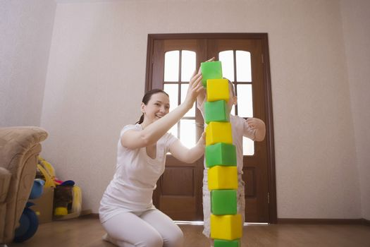 Mother and son build tower with green and yellow building blocks