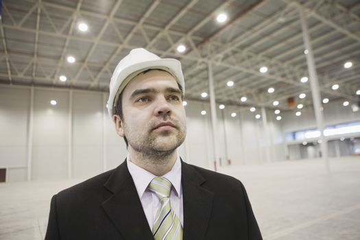 Businessman in hard hat stands in brightly lit warehouse