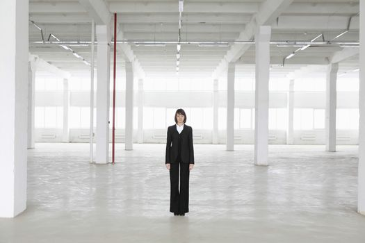 Business woman stands in empty warehouse