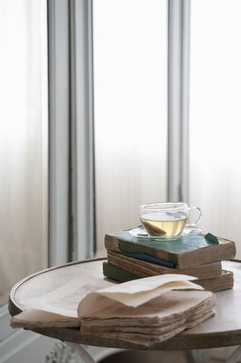 Open book on table with herbal tea in bedroom