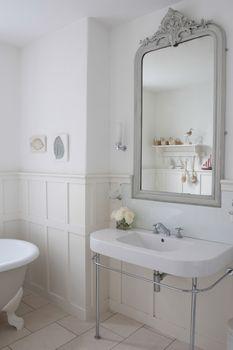 Gray painter mirror above bathroom sink