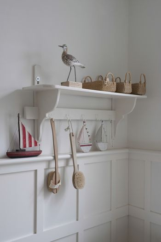 Bird statue and baskets on bathroom shelf