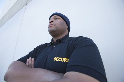 Security guard stands with arms folded