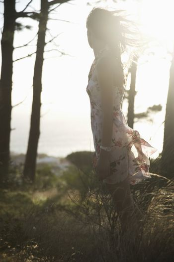 Young woman stands in summer woodland