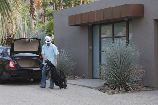 Man lifts golf bag into boot of luxury vehicle