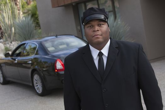 Chauffeur stands in uniform with luxury vehicle