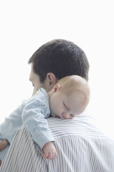 Father holds newborn on shoulder