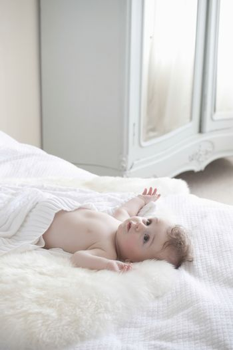 Baby boy lying on fur blanket