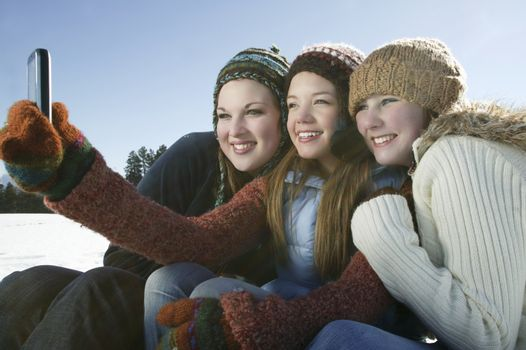 Three girls take self portrait with camera phone
