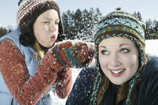 Teenage girl blows snow on her friend