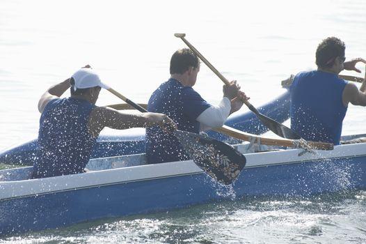 Outrigger canoeing team paddling
