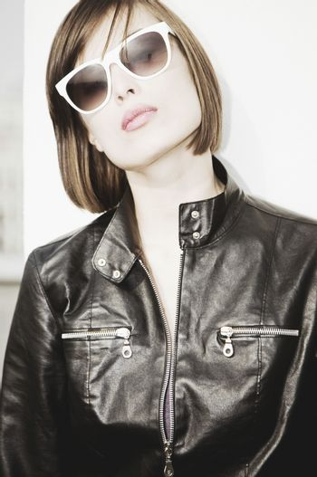 Brunette in sunglasses and black leather jacket