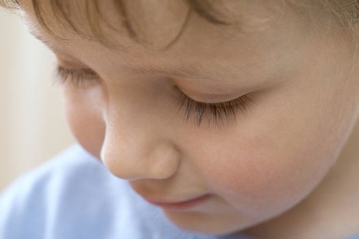 Young boy looks down concentrating