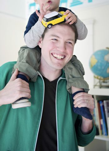 Man stands with his son on his shoulders