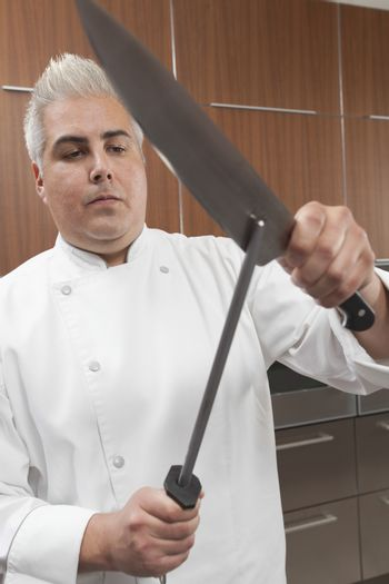Confident male chef sharpening knives in commercial kitchen